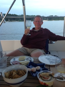 Frank drinking some special wine that Caroline brought . . . out of his trophy from the race! An etched wine glass from the Yacht Club. Okay, one real glass wine glass aboard amongst the plastic ones will work.