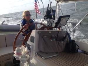 Ems behind the wheel at 8am with an unexpected 18 knots of wind. Clearly looking in need of more of the coffee sitting next to her!